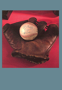 Image of Ty Cobb signed baseball from February 1, 1960. The baseball is sitting inside a leather glove of the same era.